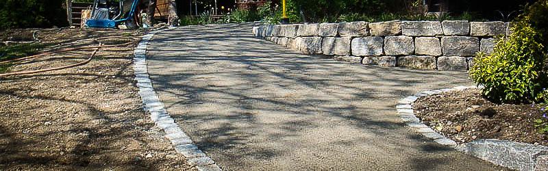 Wassergebundene Wegedecke mit Graniteinfassung als Abgang im Gelände.